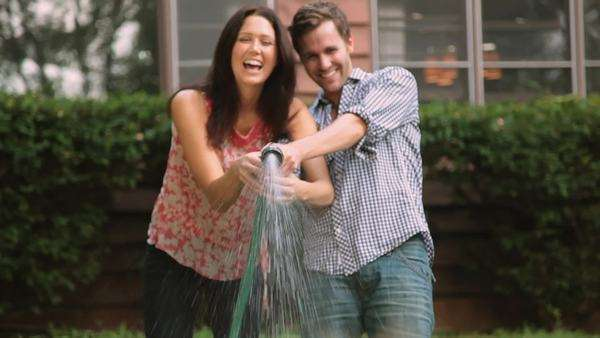 Couple playing with hose in backyard Royalty-free stock video