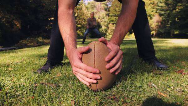 Couple playing American football in field Royalty-free stock video