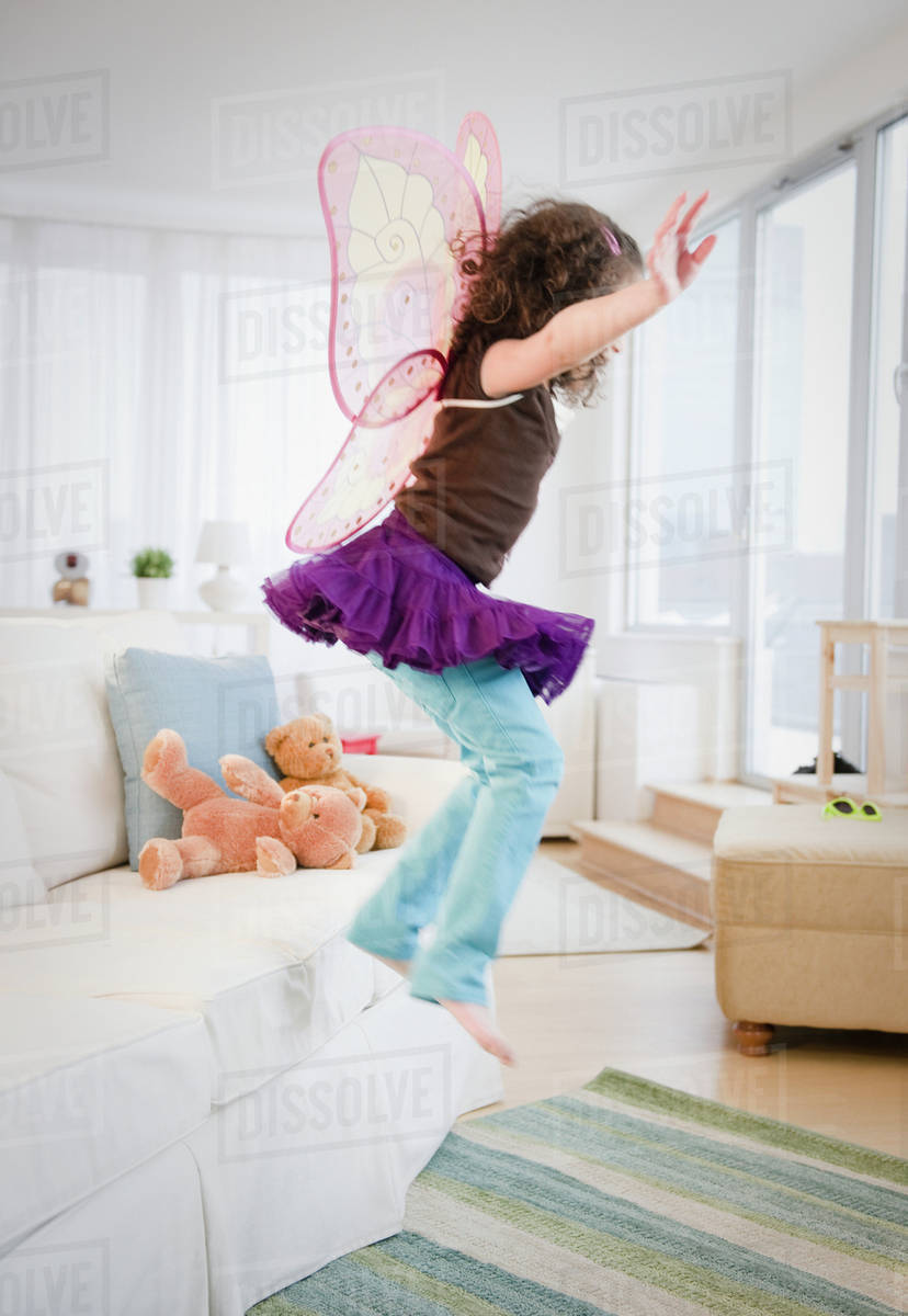 Hispanic girl in fairy wings jumping off couch Royalty-free stock photo