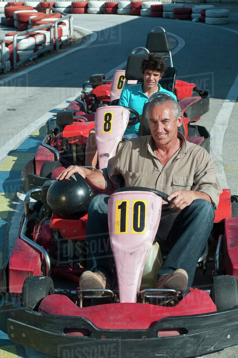 Hispanic grandfather and grandson on go-cart track stock photo