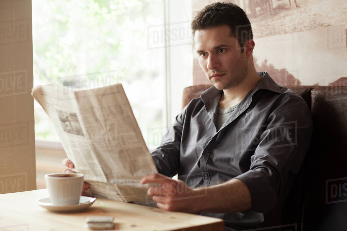 man reading newspaper and drinking coffee in cafe - stock photo