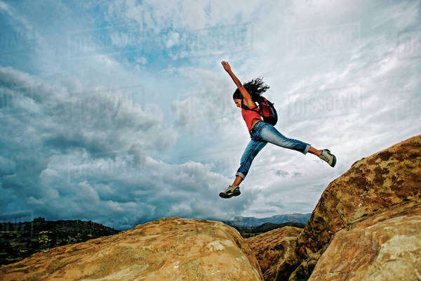 Hispanic woman jumping crevasse on rock formation Royalty-free stock photo