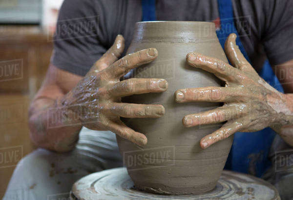 Older Caucasian man forming pottery on wheel in ceramics studio Royalty-free stock photo