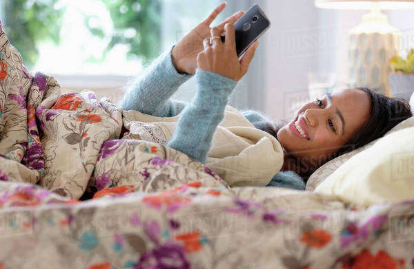 Mixed race woman using cell phone in bed Royalty-free stock photo