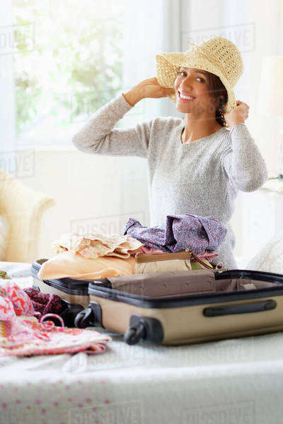 Mixed race woman packing suitcase in bed Royalty-free stock photo