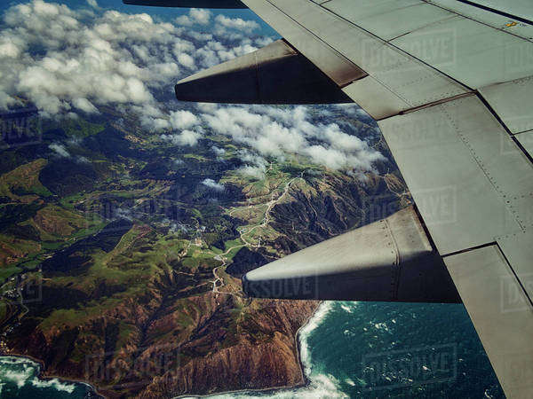 Aerial view of airplane wing flying over coastline Royalty-free stock photo