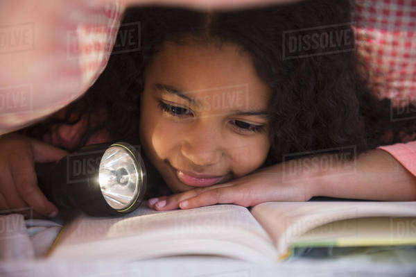 Mixed race girl reading book with flashlight under blanket Royalty-free stock photo