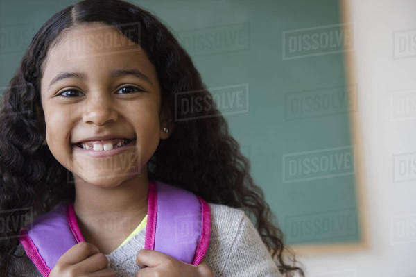 Smiling mixed race student wearing backpack in classroom Royalty-free stock photo