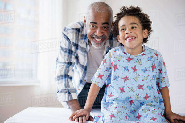 Mixed race grandfather smiling with grandson in hospital Royalty-free stock photo