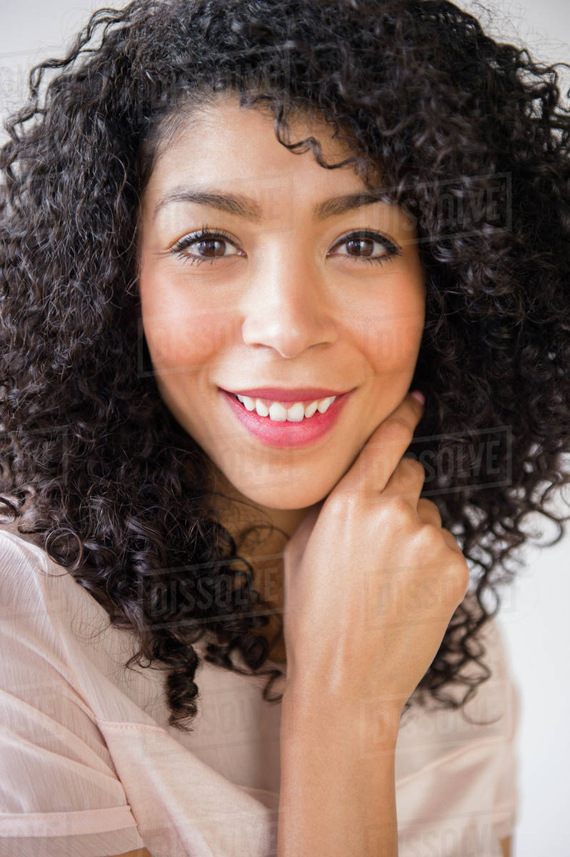 Mixed race woman with curly hair smiling - Stock Photo ...