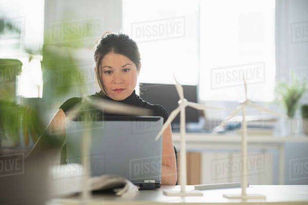 Mixed race architect with windmill models working on laptop Royalty-free stock photo
