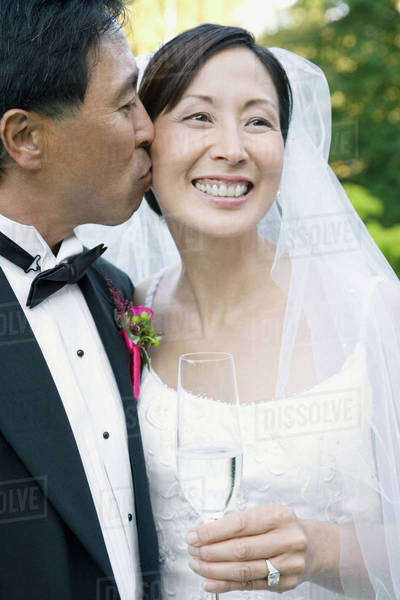 Asian groom kissing bride's cheek Royalty-free stock photo