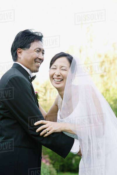 Asian newlyweds laughing Royalty-free stock photo