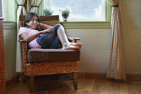 Hispanic girl sitting in armchair Royalty-free stock photo