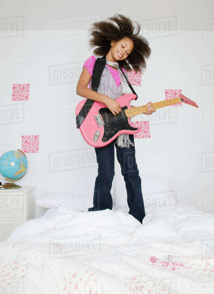 African girl playing guitar on bed Royalty-free stock photo