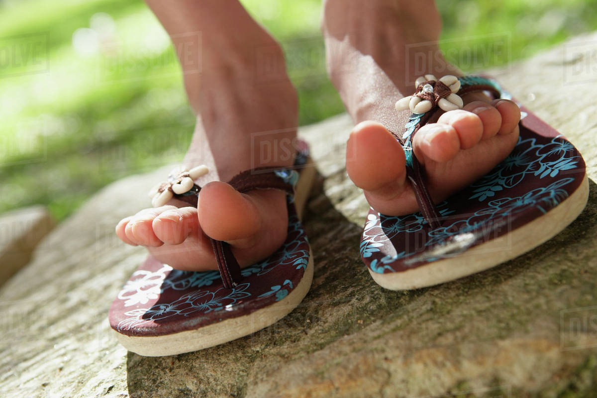 22f78a7d8bc025 Close up of girl s feet in flip flops outdoors - Stock Photo - Dissolve