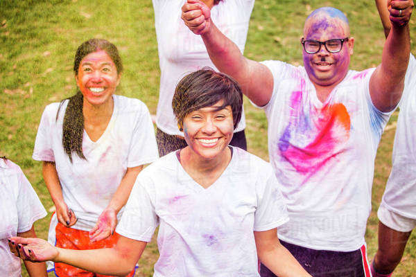 Smiling friends covered in pigment powder cheering Royalty-free stock photo