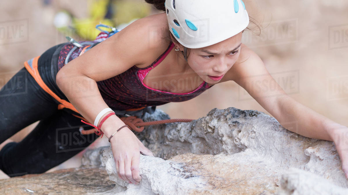 Mixed race girl climbing rock wall Royalty-free stock photo