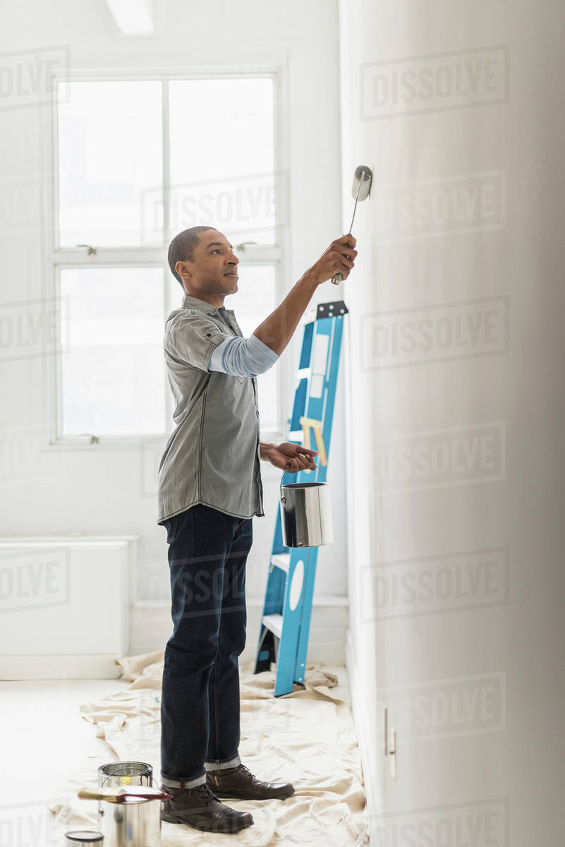 Black man painting wall of home stock photo