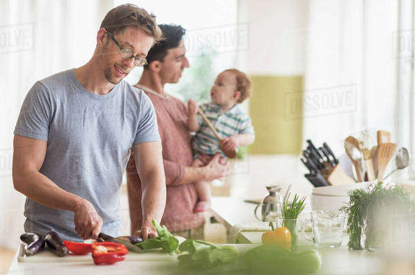Caucasian gay fathers and baby cooking in kitchen Royalty-free stock photo