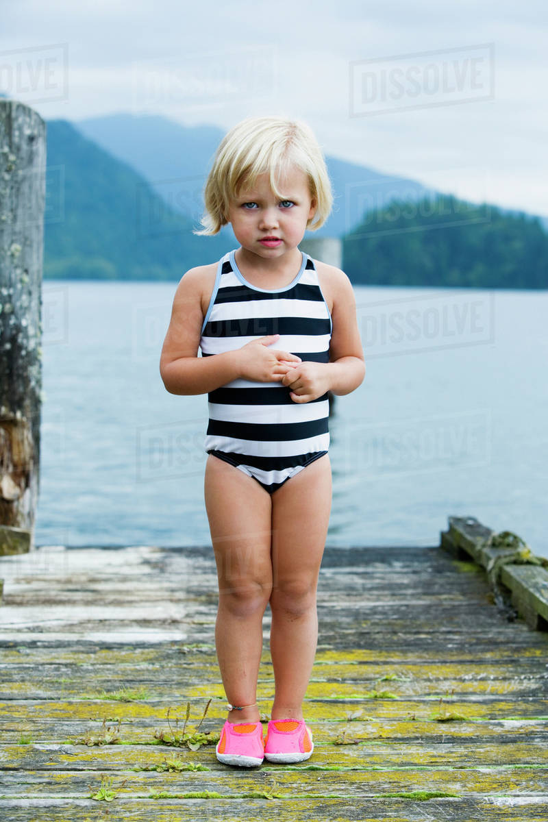 e465457689133 Young girl in bathing suit standing on wooden pier - Stock Photo ...