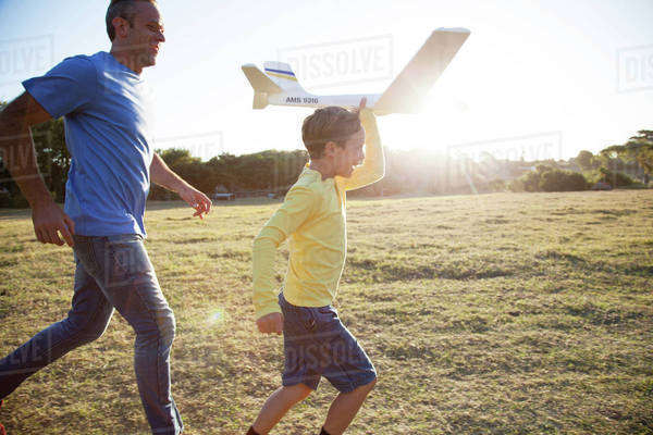Caucasian father and son flying model airplane in field Royalty-free stock photo