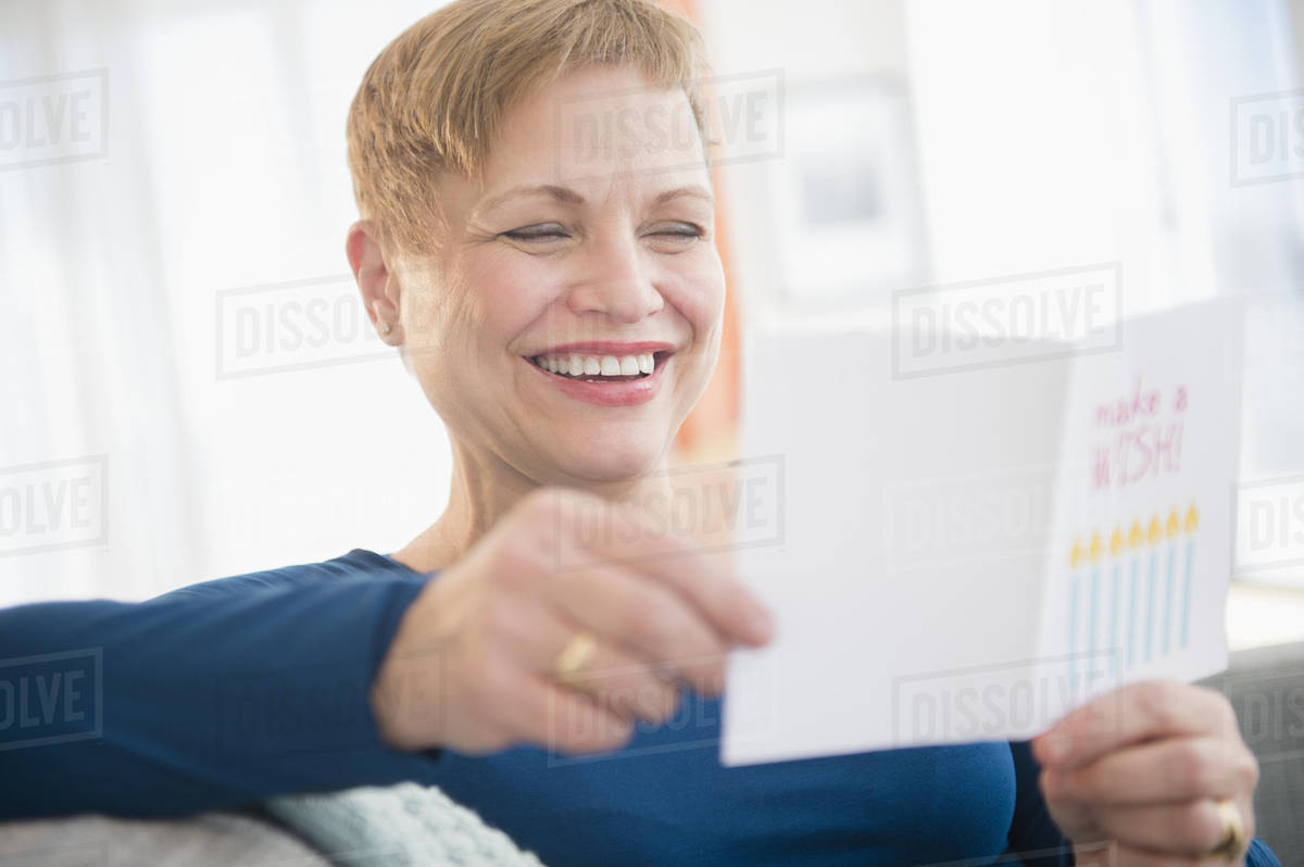 Caucasian woman reading birthday card D5_5_5