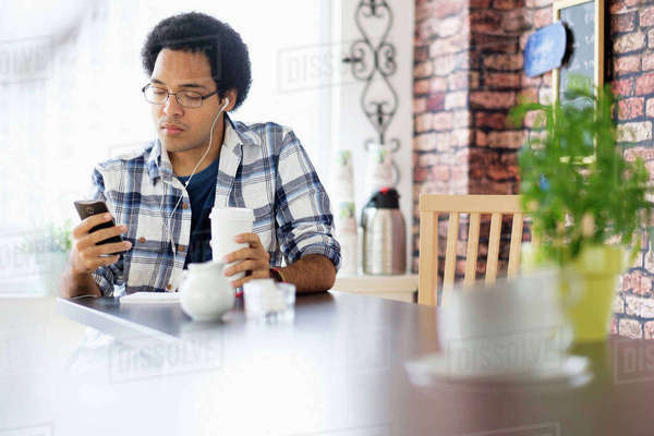 Mixed race man using cell phone in coffee shop Royalty-free stock photo