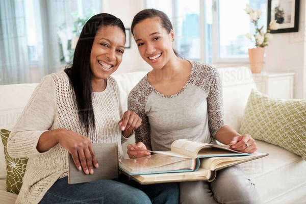 Mother and daughter looking at photo album on sofa Royalty-free stock photo