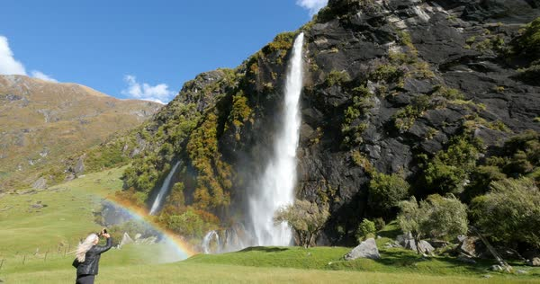 Woman photographing rainbow near mountain waterfall Royalty-free stock video