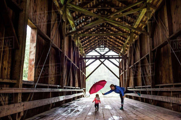 Caucasian mother and baby daughter on covered bridge Royalty-free stock photo
