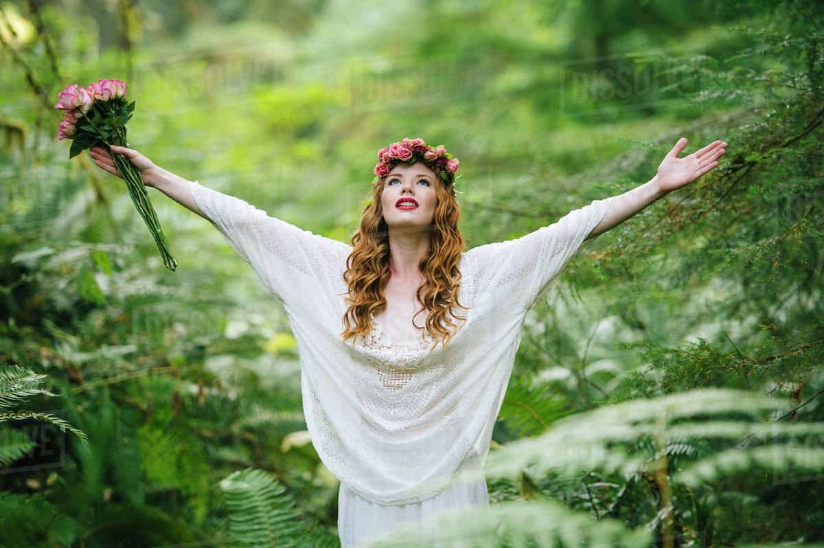 Caucasian Woman Wearing Flower Crown In Forest Stock Photo Dissolve