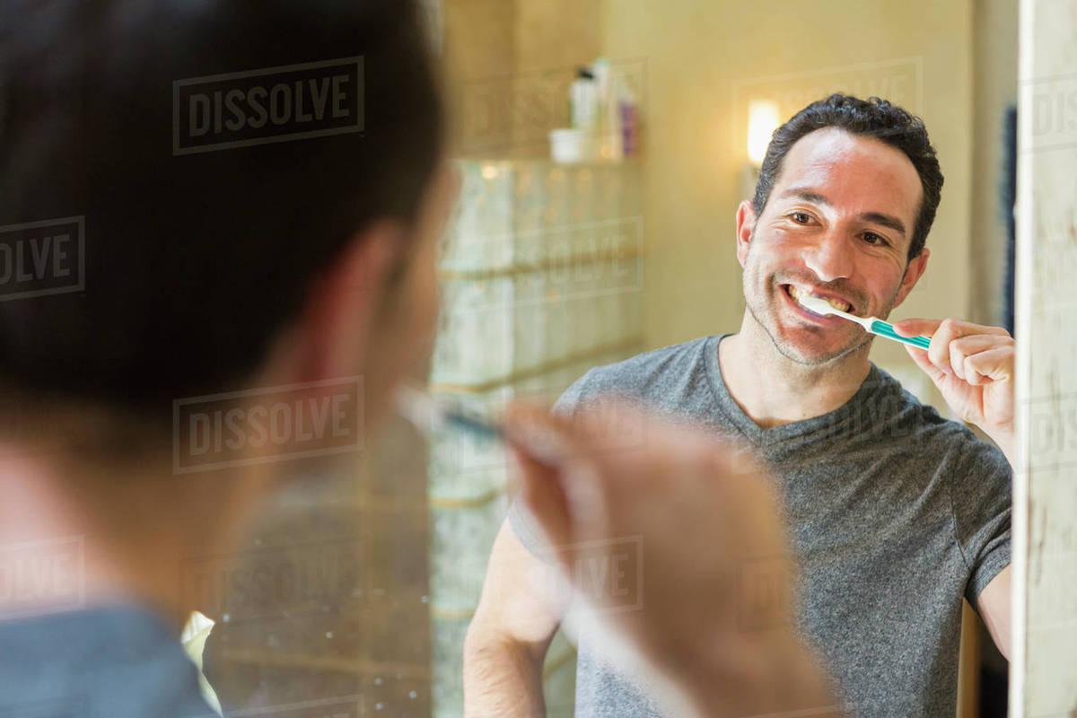 Candid asian mature brushing teeth
