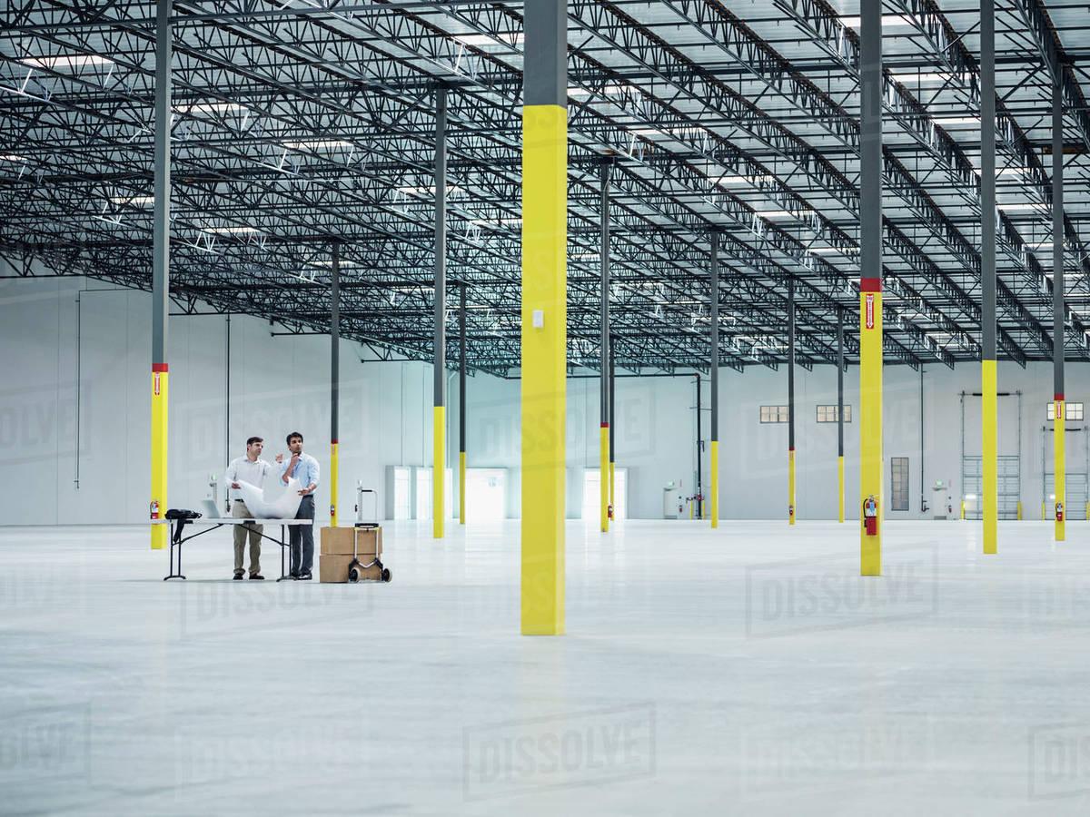 Architects using blueprint in empty warehouse stock photo dissolve architects using blueprint in empty warehouse malvernweather Choice Image