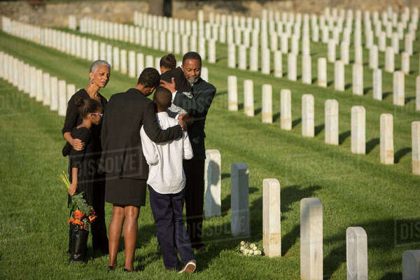 Multi-generation Black family hugging in military cemetery Royalty-free stock photo
