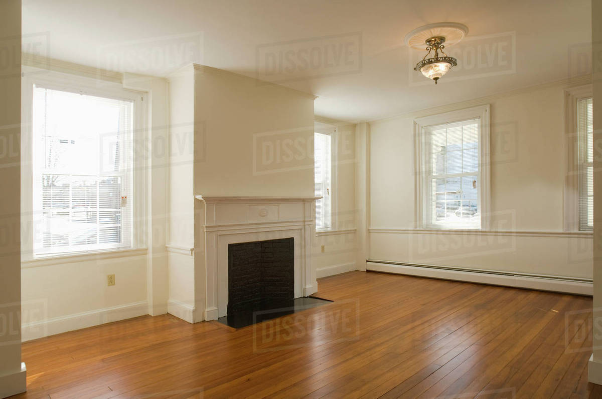 Empty Room In Apartment With Hardwood Floor And Fireplace