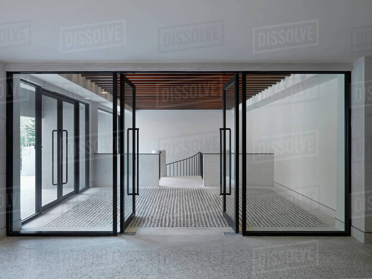 Modern Entrance Foyer With Glass Doors And Stone Floor Stock Photo