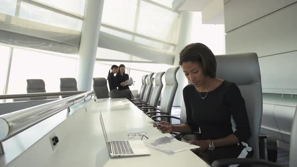Businesswoman reading paperwork and texting in spacious conference room Royalty-free stock video