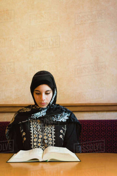Middle Eastern teenager in headscarf reading book Royalty-free stock photo