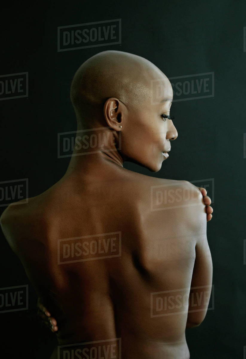 Nude African American woman looking over her shoulder - Stock Photo ...