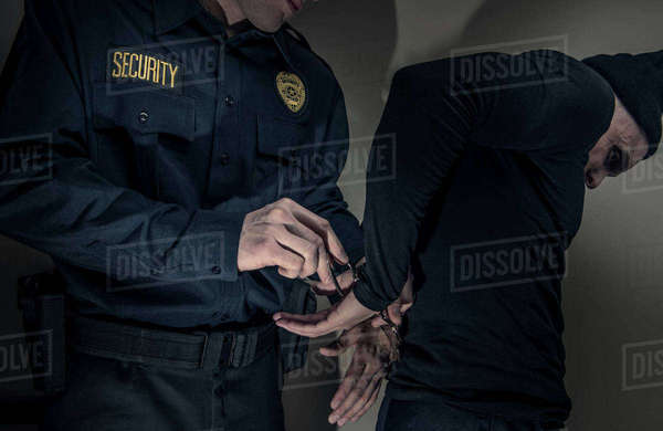 Caucasian police officer handcuffing burglar Royalty-free stock photo