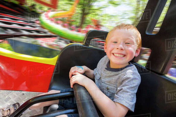 Caucasian boy smiling on amusement park ride Royalty-free stock photo