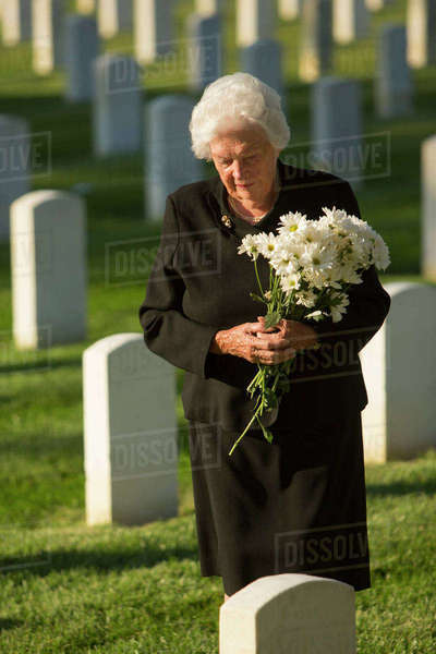 Caucasian widow holding bouquet at cemetery gravestone Royalty-free stock photo