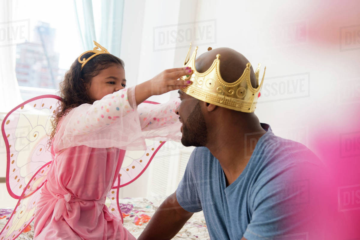 Daughter wearing costume placing crown on father Royalty-free stock photo