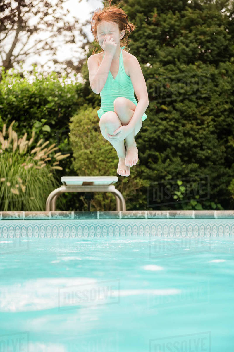 Caucasian girl holding nose jumping off diving board into swimming ...