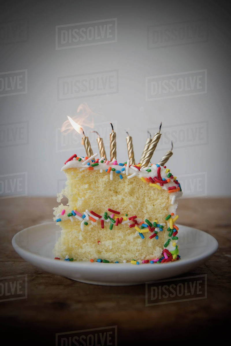 Flickering Candle Burning Cake With Sprinkles On Plate