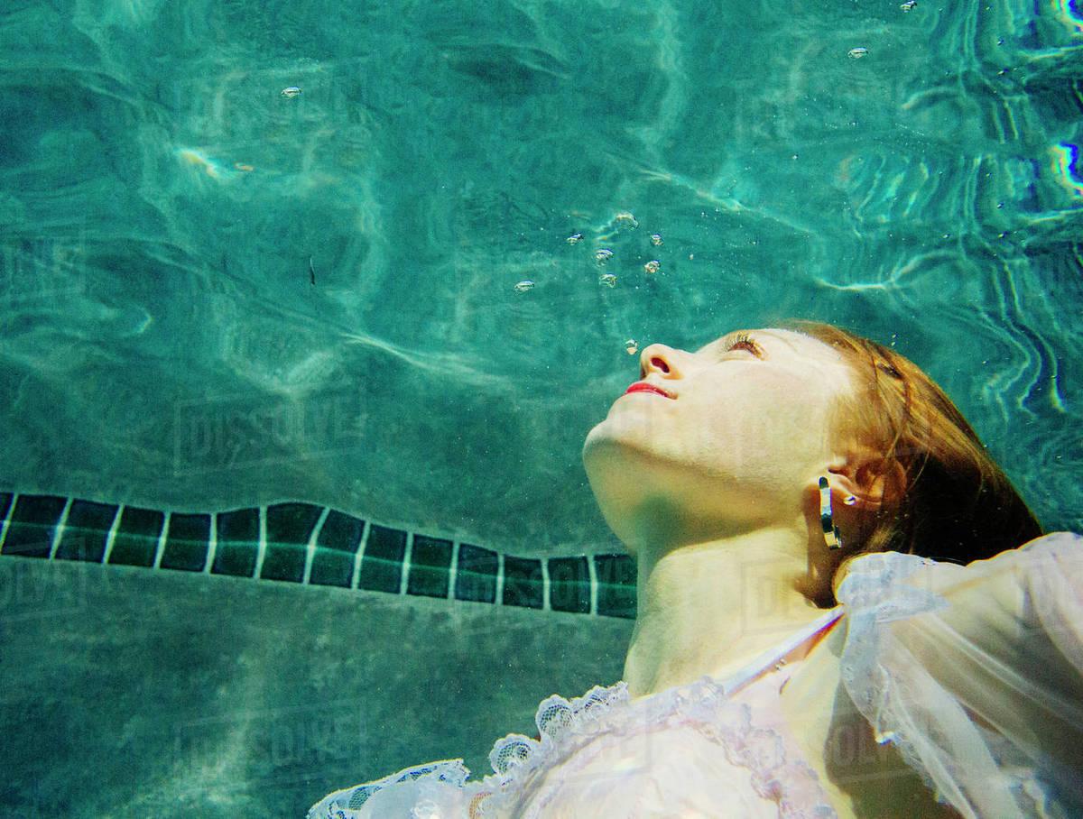 de5205f697 Caucasian woman wearing dress swimming underwater - Stock Photo ...