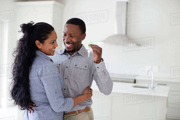Couple hugging and holding keys in new home Royalty-free stock photo