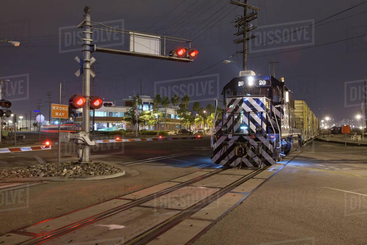 Train at railroad crossing at night stock photo