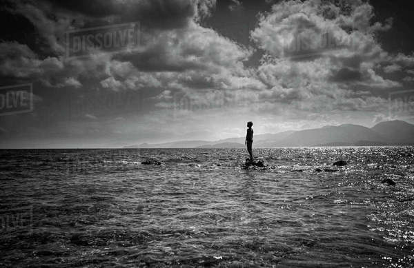 Silhouette of Caucasian boy standing on rock in ocean Royalty-free stock photo